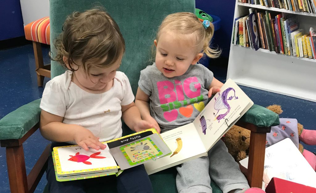 2 little girls reading books together